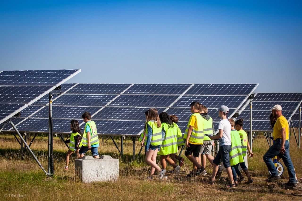groep wandelt tussen de zonnepanelen op de zonneberg
