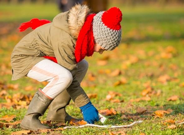 een kind raapt een touw op dat in het gras ligt